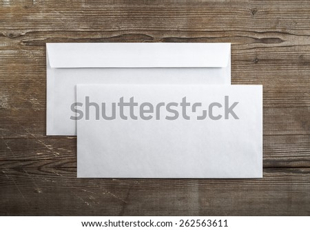 Photo of blank envelopes on a dark wooden background. Back and front. Template for branding identity. Top view. - stock photo