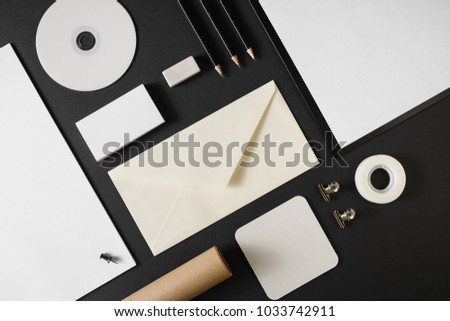 Photo of blank stationery template for placing your design. Mockup for branding identity on black paper background. Top view.