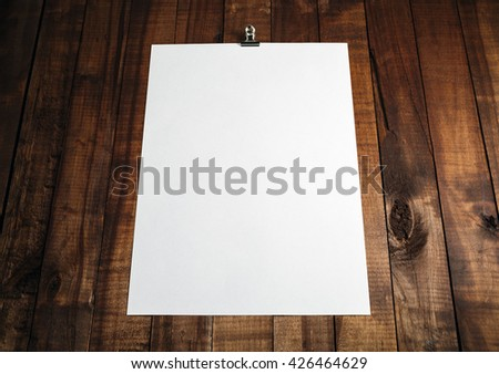 Photo of blank white paper poster on vintage wooden table background. Blank sheet of paper with plenty of copy space. Mock-up for design portfolios. - stock photo