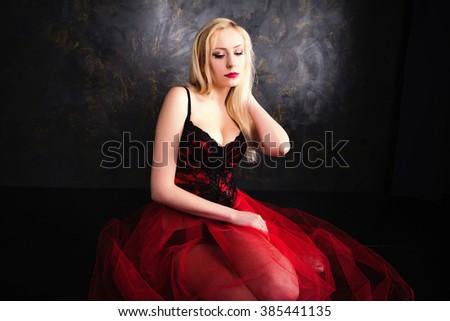 photo of blond woman wearing beautiful long red skirt and corset - stock photo