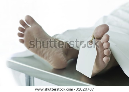 Photo of body covered with a sheet in a morgue, feet toward camera with blank tag on the big toe. Feet are clean and smooth. (body is a model) - stock photo