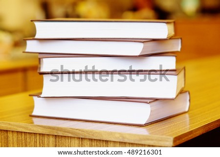 photo of books on yellow wooden deck tabletop