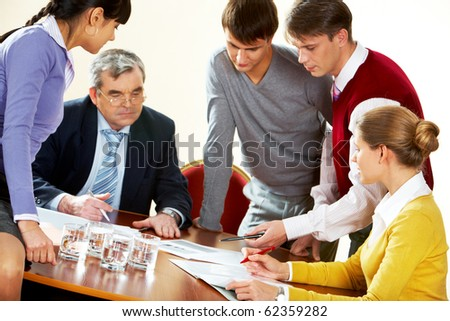 Photo of boss surrounded by colleagues during discussion - stock photo