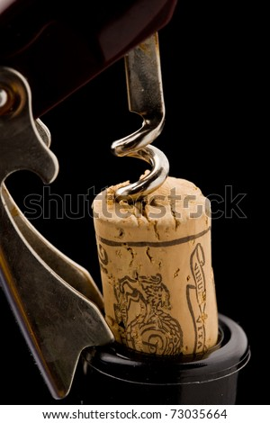 photo of bottle opener on black background pulling a cork outside of the bottle - stock photo