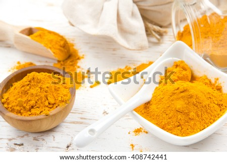 Photo of bowls full of curry powder on white wooden surface