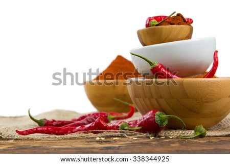 Photo of bowls full of red pepper spice on burlap and wooden board - stock photo