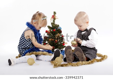 photo of boy and girl decorate the Christmas tree