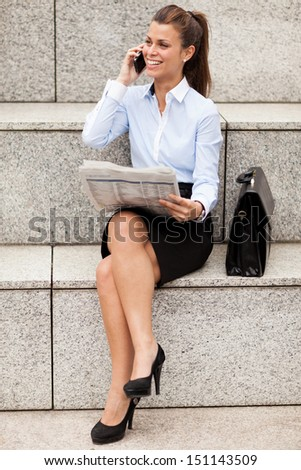 photo of brunette businesswoman sitting on stairs with newspaper - stock photo