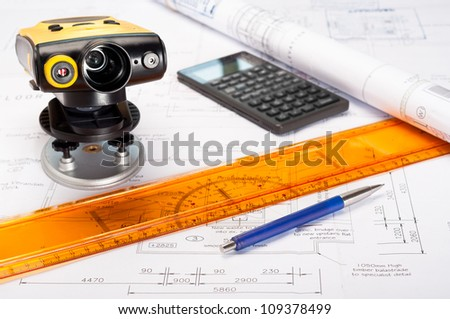 Photo of building plans with laser measurement device and drawing tools - stock photo