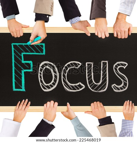 Photo of business hands holding blackboard and writing FOCUS concept - stock photo