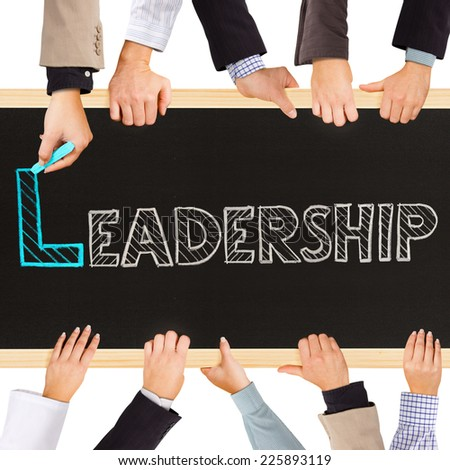 Photo of business hands holding blackboard and writing LEADERSHIP concept - stock photo