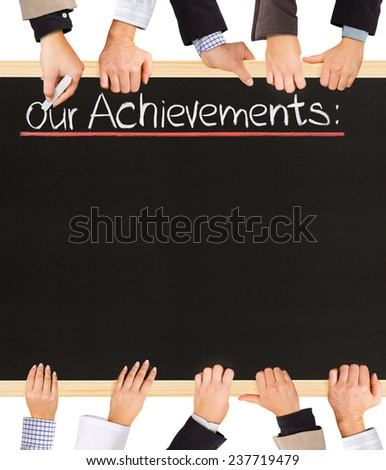 Photo of business hands holding blackboard and writing Our Achievements - stock photo
