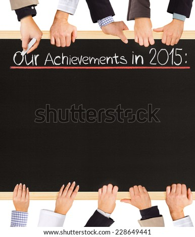 Photo of business hands holding blackboard and writing Our Achievements in 2015 - stock photo