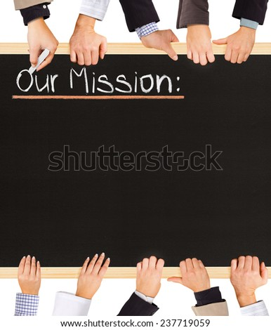 Photo of business hands holding blackboard and writing Our Mission - stock photo