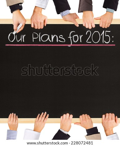 Photo of business hands holding blackboard and writing Our Plans for 2015 - stock photo