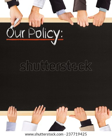 Photo of business hands holding blackboard and writing Our Policy - stock photo