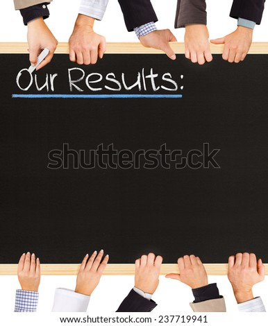 Photo of business hands holding blackboard and writing Our Results - stock photo