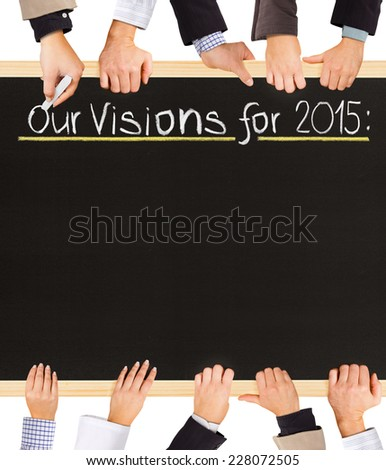 Photo of business hands holding blackboard and writing Our Visions - stock photo
