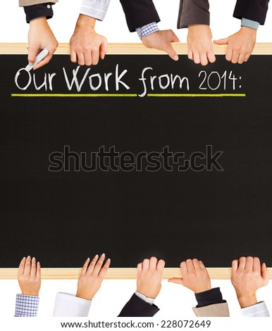 Photo of business hands holding blackboard and writing Our Work from 2014 - stock photo