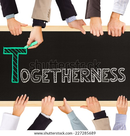 Photo of business hands holding blackboard and writing TOGETHERNESS concept - stock photo