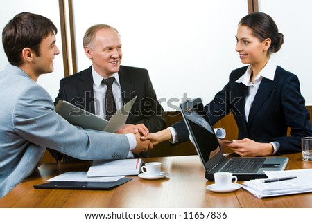 Photo of business partners holding hands making a consensus - stock photo