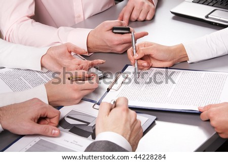 Photo of business people hands working with documents at briefing
