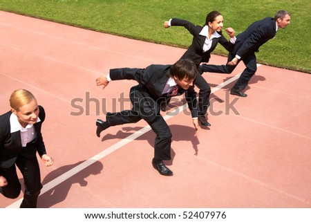 Photo of business people running on sport track - stock photo