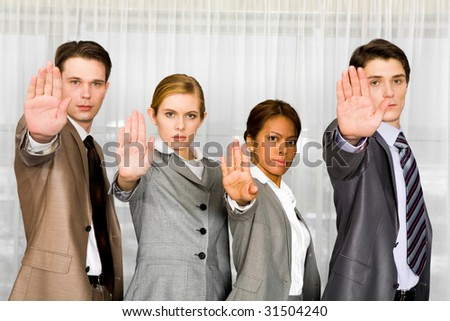 Photo of business people standing in line and showing stop sign by their palms - stock photo