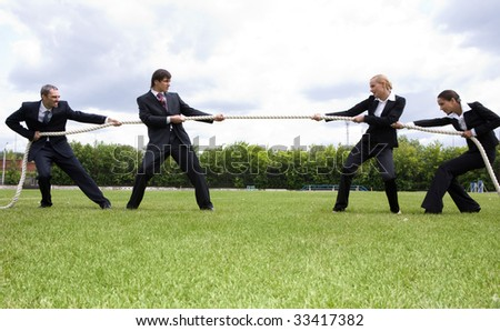 Photo of business people stretching the rope in the stadium - stock photo