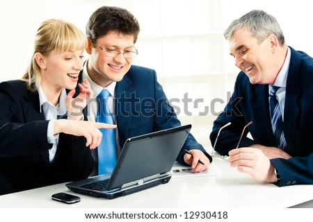 Photo of  business team sitting at the table with laptop on it and looking at its screen while smiling woman pointing at monitor - stock photo