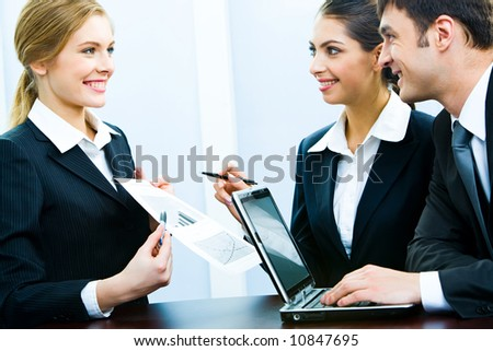 Photo of business woman demonstrating her project to coworkers - stock photo