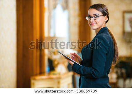 Photo of business woman in expensive hotel. Young business woman wearing suit and glasses, standing in nice hotel room, using tablet computer and looking at camera - stock photo