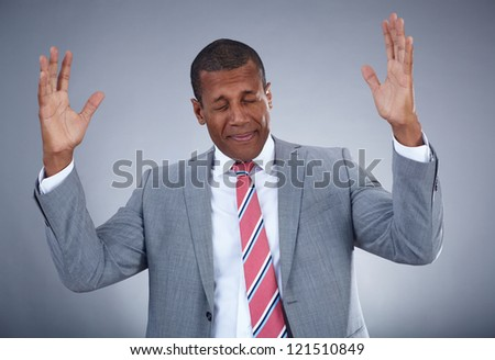 Photo of businessman expressing confusion on grey background - stock photo