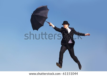 Photo of businessman flying on umbrella with blue sky at background - stock photo