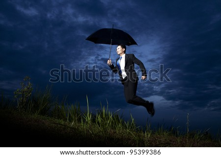 Photo of businessman flying with umbrella on dark