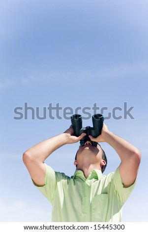 Photo of businessman in casual clothing looking through binoculars - stock photo