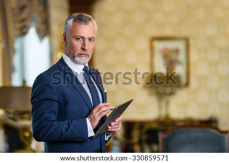 Photo of businessman in expensive hotel. Aged businessman wearing suit, standing in nice hotel room, using tablet computer and looking at camera - stock photo