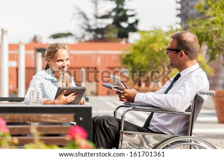 Photo of businessman on wheelchair talks to his colleague - stock photo