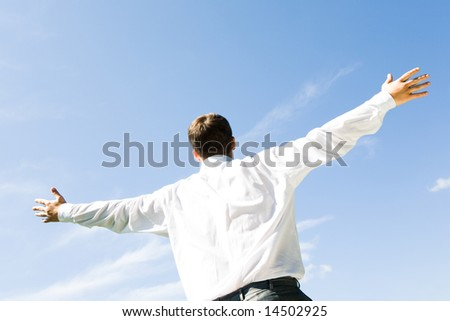Photo of businessman standing with his arms stretched on the background of blue sky - stock photo