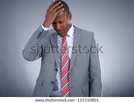 Photo of businessman touching his head on grey background - stock photo