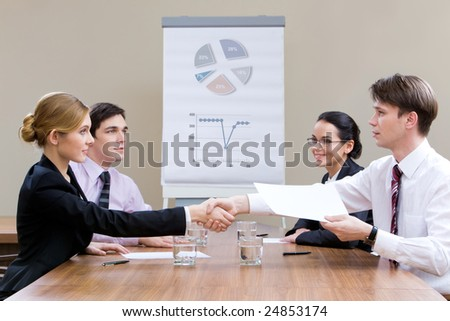 Photo of businesspartners shaking hands after making an agreement with their co-workers looking at them