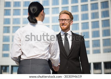 Photo of businesspeople shaking hands. Two cheerful business partners handshaking and smiling near office building.