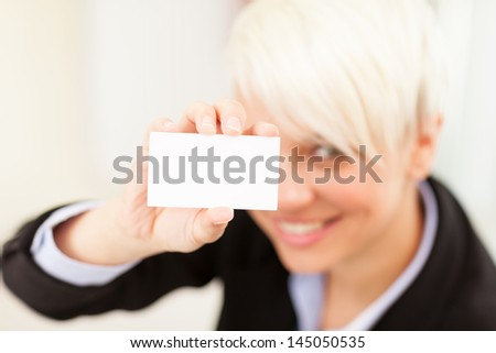 Photo of businesswoman holding business card while smiling - stock photo