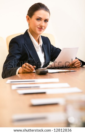 Photo of businesswoman sitting in the workshop and looking at camera with papers in hand - stock photo