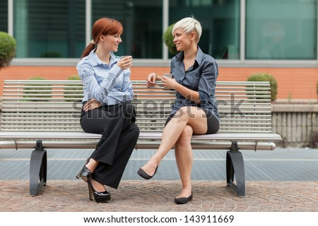 photo of businesswoman sitting outside on a bench and talking - stock photo