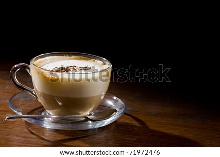 photo of cappuccino in glass cup on wood table - stock photo