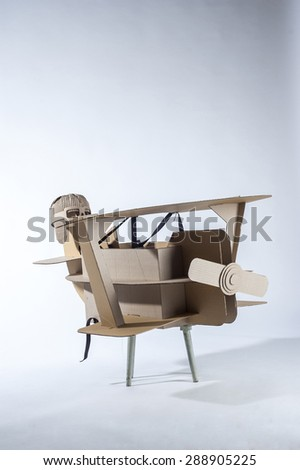 Photo of  cardboard plane and aviator hat on white background.  - stock photo