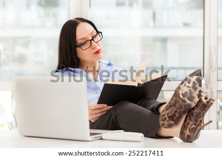 Photo of caucasian businesswoman reading a book in the office with legs on the desk - stock photo