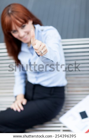 Photo of caucasian businesswoman sitting on a metal bench and making positive thumb gesture - stock photo