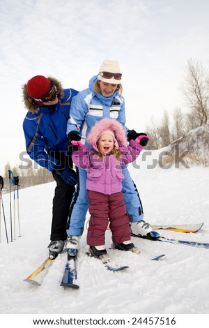 Photo of Caucasian family fond of skiing on mountainside in winter - stock photo